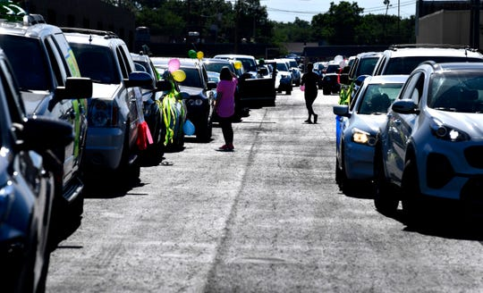 Drivers step between vehicles and attach decorations as they prepare in a parking lot near S. 27th Street for a neighborhood parade honoring Georgiana Reagan Thursday.