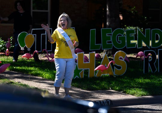Georgiana Reagan waves at the parade of cars rolling past her home Thursday. Reagan in June is retiring in June from her position as director of the Early Head Start program in the Abilene Independent School District.