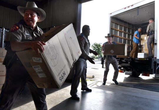 Gilbert Valdez hands a box to the next man behind him as a line of DPS Troopers unload a truck filled with personal protective equipment May 21.