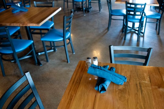 Empty tables are pictured on Wednesday, May 20, 2020 at Lucky Rooster Kitchen & Cocktails in Battle Creek, Mich. The Lucky Rooster is implementing a new reservation system that will launch as dining rooms in Michigan restaurants reopen after the shutdown.