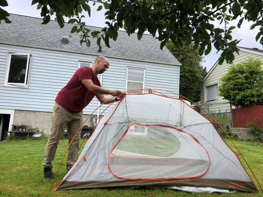 """Manette resident Dane Sellers sets up a tent in his backyard. """"It's the starlight, its' the fire, it's being able to sleep out and under the stars,"""" said Sellers, who's camped two weekends since the COVID-19 pandemic began."""