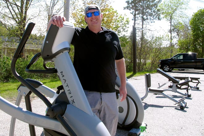 Sean Manovill, owner of Club Fitness of Vermont, poses with exercise equipment he moved outside so the Rutland, Vt., gym could reopen on Tuesday, May 19, 2020. The Vermont attorney general sued him and the fitness center for being open on Friday, which he said was against the state rules amid the coronavirus outbreak, and judge granted an order to temporarily close it.