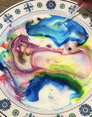 Food coloring creates a rainbow to demonstrate surface tension.