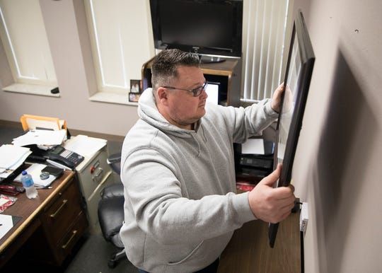 Former Chillicothe Chief of Police Keith Washburn finishes removing items from his wall as he gets ready for his new job as an assistant prosecutor for Jackson County.