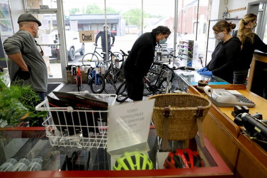 Megan Ausdenmoore, second from the right, assists customers inside the store as another waits outside, Thursday, May 21, 2020, at Jim's Bicycle Shop in Deer Park, Ohio. The shop is limited to two customers at a time. There has been a surge in bicycle sales since the beginning of the new coronavirus pandemic.