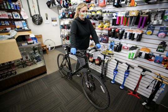 Alison Peters pushes a bike in need of repair to the back of the store, Thursday, May 21, 2020, at Jim's Bicycle Shop in Deer Park, Ohio. The shop is limited to two customers at a time. There has been a surge in bicycle sales since the beginning of the new coronavirus pandemic.
