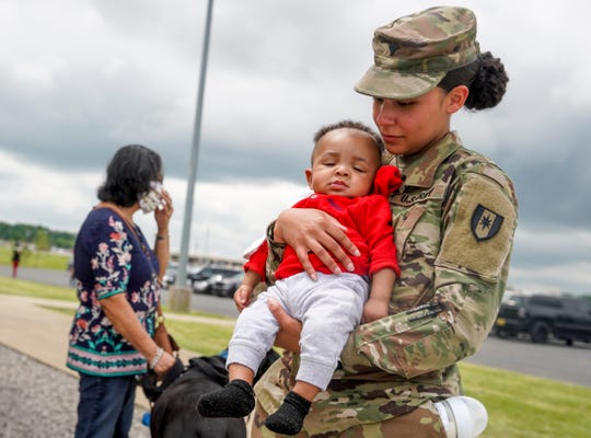 SPC Ericka Price holds onto Bryson Bentley, 5 months, as they wait to see SG Bryant Bentley during a welcome home ceremony for soldiers from the 531st Hospital Center that had been deployed to New York to help at the Division Parade Field in Fort Campbell, KY., on Thursday, May 21, 2020.