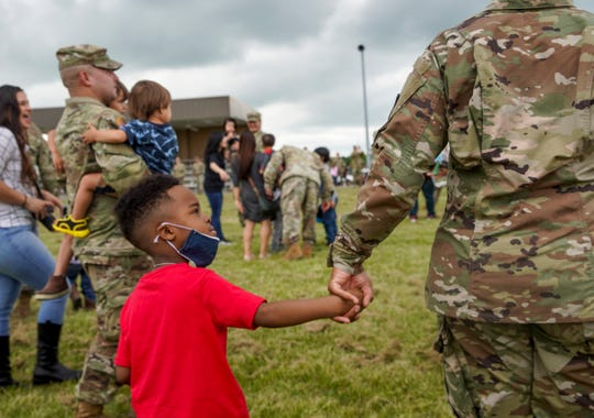 1SG Leqwenda Johnson walks off the field with her son, Kennedy Johnson, 4, during a welcome home ceremony for soldiers from the 531st Hospital Center that had been deployed to New York to help at the Division Parade Field in Fort Campbell, KY., on Thursday, May 21, 2020.
