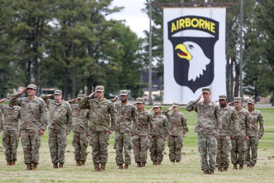 Soldiers stand saluting before being allowed to rest  and their families to greet them across the field during a welcome home ceremony for soldiers from the 531st Hospital Center that had been deployed to New York to help at the Division Parade Field in Fort Campbell, KY., on Thursday, May 21, 2020.
