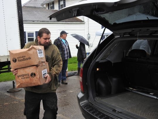 Volunteer Jeremy Dushal of the Upper Room Assembly and Worship Center puts boxes from the Mid-Ohio Food Bank into a vehicle during the church's recent food distribution day. Despite a steady rain, more than 55,000 pounds of food was given out to about 400 families.