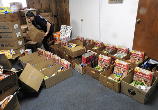 Nichole Braxton sorts through food from the Mid-Ohio Food Bank in the basement of Upper Room Assembly and Worship Center. More then 55,000 pounds of food was given out recently to 400 families in need.