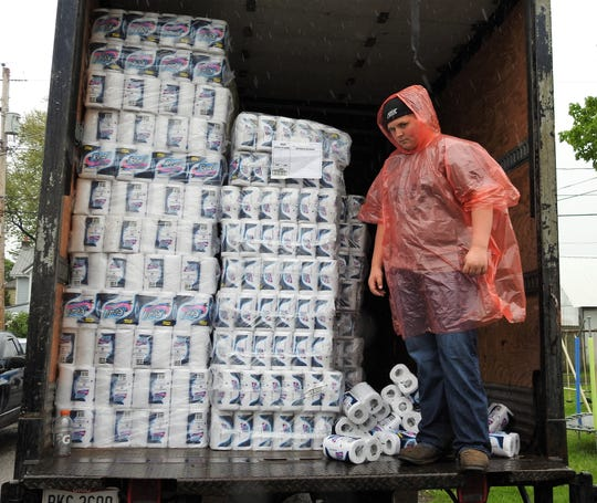 Kaden DeWitt stands in the back of a semi-trailer filled with toilet paper for distribution to those in need at the Upper Room Assembly and Worship Center. Families were allowed one pack of toilet paper each.