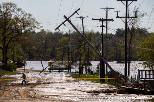 A person crosses the road next to the Sanford Dam where debris washed over the roadway May 20, 2020. Many homes and business in and around downtown were overcome by flood waters when the Sanford Dam failed.