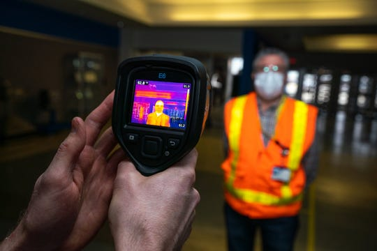 Jamie Chatel, Senior Launch Engineer for GM, left and Joe Mizzi, GM Mask Operations manager, demonstrates how the FLIR thermal scanner shows body temperature.