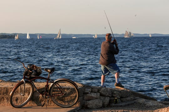 A fisherman awaits a catch as the sun sets on Grand Traverse Bay in Traverse City.