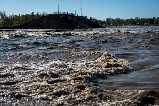 Water rushes past the remainder of the Edenville Dam at Wixom Lake in Beaverton, Mich. on Wednesday, May 20, 2020.