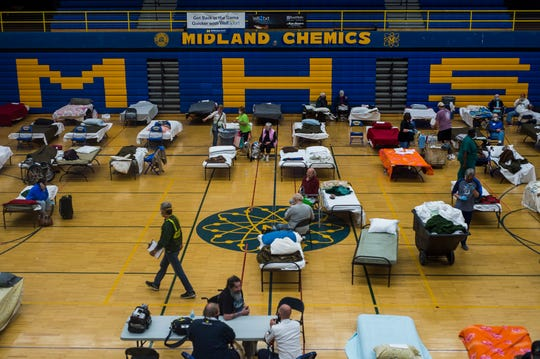 Volunteers assist evacuated residents at a temporary shelter at Midland High School, Wednesday.