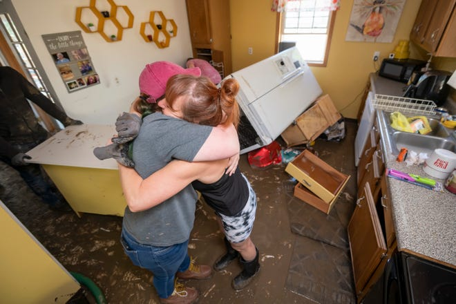 Rebecca Johnson, right, hugs her niece, Paige Benjamin, as Johnson cleans out the kitchen of her home in Sanford on Thursday.