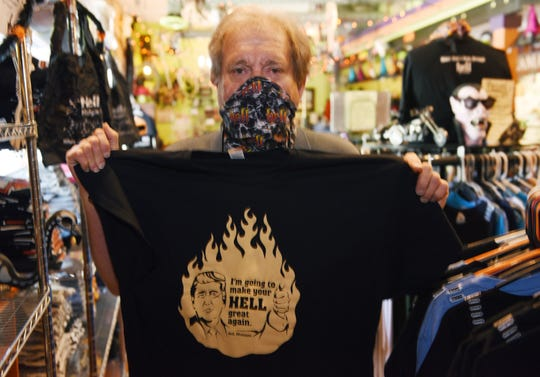 John Colone shows off a T-shirt from his souvenir shop.