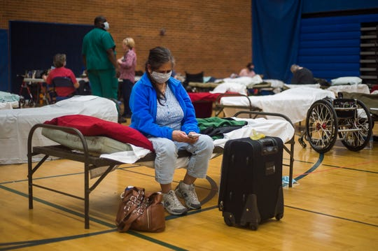Midland resident Ritu Patel communicates with family members on her cell phone at a temporary shelter at Midland High School, Wednesday, May 20, 2020 in Midland, Mich. Patel was concerned because her husband had left the shelter to assess the flood damage to their home.