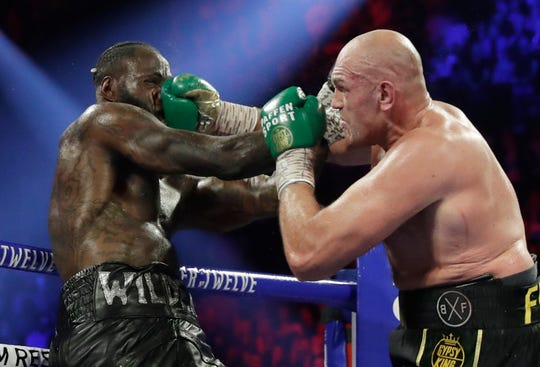 Tyson Fury lands a right to Deontay Wilder, left, during a WBC heavyweight championship boxing match in Las Vegas earlier this year.