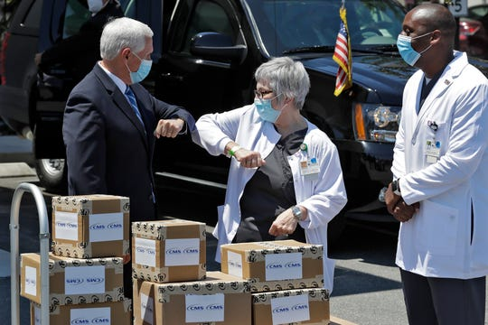 Vice President Mike Pence, left, greets director of nursing Shirley Schultz and health service administrator Fanley Romelus, right, after delivering personal protective equipment to the Westminster Baldwin Park, Wednesday, May 20, 2020, in Orlando, Fla., as part of the initiative to deliver PPE to more than 15,000 nursing homes across America.