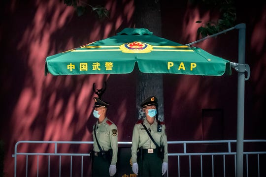 In this Wednesday, May 20, 2020, photo, Chinese paramilitary police stand guard near Tiananmen Square and the Great Hall of the People in Beijing. This year's version of China's biggest political meeting of the year will be unlike any other.