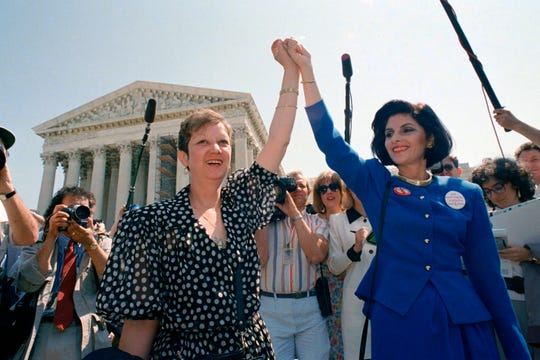In this April 26, 1989 photo, Norma McCorvey, Jane Roe in the 1973 court case, left, and her attorney Gloria Allred hold hands as they leave the Supreme Court building in Washington after sitting in while the court listened to arguments in a Missouri abortion case.