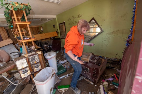 Connie Methner, owner of CJ's Hairstyling, wades through the mud covering the inside of her salon in Sanford, Thursday. The Mid-Michigan village was hit especially hard by flood waters after the Sanford dam failed earlier in the week.