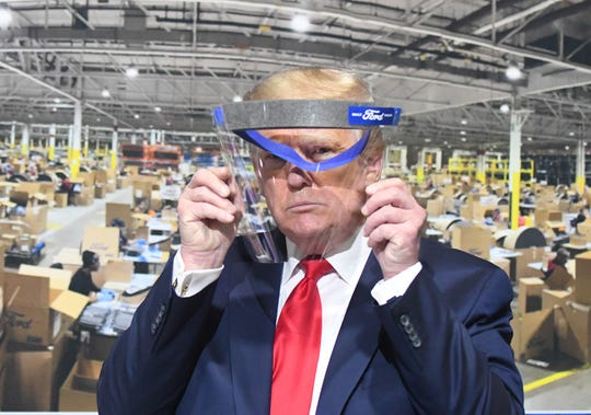 President Trump looks through a face shield, in front of poster of the manufacturing of these shields, while touring Ford Motor Company's Rawsonville Components Plant  in Ypsilanti, Michigan on May 21, 2020.