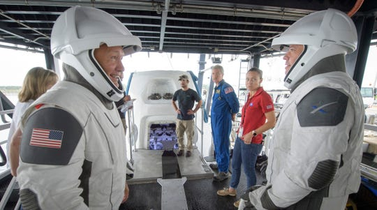 FILE - In this Aug. 13, 2019 file photo, NASA astronauts Doug Hurley, left, and Bob Behnken work with teams from NASA and SpaceX to rehearse crew extraction from SpaceX's Crew Dragon, which will be used to carry humans to the International Space Station, at the Trident Basin in Cape Canaveral, Fla.