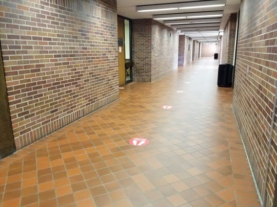 Red circles placed six feet apart on the floor indicate where to stand to maintain social distance in the Civic Center's court building.