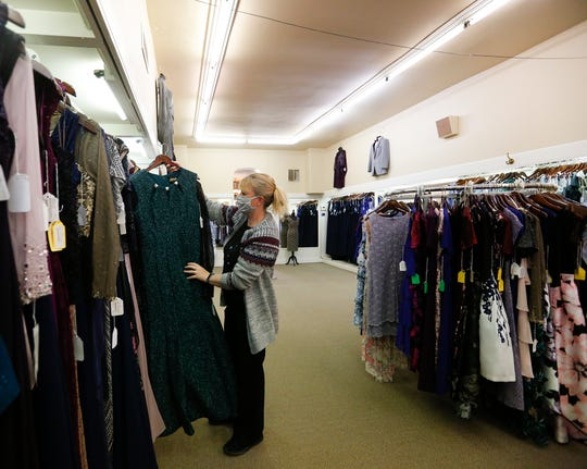 Kim Heinemann puts a dress away at Edith's Bridal and Tuxedo in Fond du Lac. The store reopened May 15, more than two months after it closed due to concerns about the coronavirus.