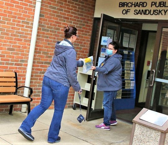 Staff member, Krista Paul hands out books that were ordered online, at the Birchard Public Library.