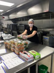 Chasity O'Neill owner of Vaguely Vegan completes her order of fresh salads for the week.