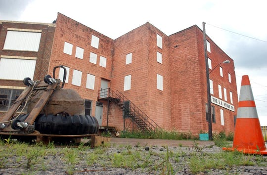 A wrecking ball at left sits outside the S.E. Hyman Co. building along Concord Street in July 2005 to prepare to demolish the Fremont building where winter gear including snowmobile suits and winter jackets was produced.