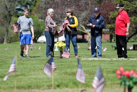 Volunteers help the American Legion Post 11 Sullivan Wallen Green Bay on Wednesday, May 20, 2020, place flags on the graves of military veterans for Memorial Day at Nicolet Memorial Gardens cemetery in Green Bay, Wis.