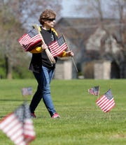 Air Force veteran Renee Jackson volunteers with the American Legion Post 11 Sullivan Wallen Green Bay on Wednesday, May 20, 2020, to place flags on the graves of military veterans for Memorial Day at Nicolet Memorial Gardens cemetery in Green Bay, Wis.
