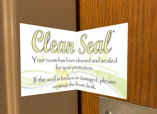 """A 2"""" by 4"""" Clean Seal sticker slides between a door and its frame to show a hospitality room has not been touched between it being sanitized and guests arriving."""