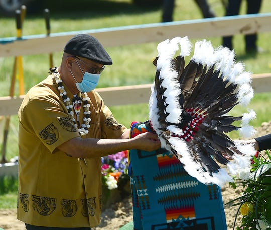 In this May 2, 2020 photo, Tafuna Tulsi Sr. ties a headdress over the grave as friends and family gather for the funeral of Bruce Spotted Bear Sr. on his ranch near Pryor, Mont. Spotted Bear and his son Bruce Spotted Bear Jr. both died of coronavirus within a few days of each other. (Larry Mayer/The Billings Gazette via AP)
