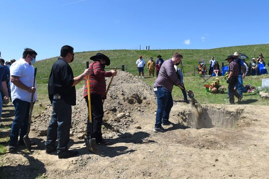 In this May 2, 2020 photo, friends and family shovel dirt into the grave at the funeral for Bruce Spotted Bear Sr. on his ranch near Pryor, Mont. Spotted Bear and his son Bruce Spotted Bear Jr. both died of coronavirus within a few days of each other. (Larry Mayer/The Billings Gazette via AP)