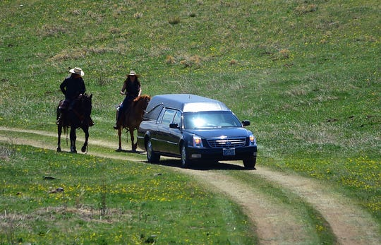 In this May 2, 2020 photo, riders on horses accompany a Dahl Funeral Chapel hearse as friends and family gather for the funeral of Bruce Spotted Bear, Sr. on his ranch near Pryor, Mont. Spotted Bear and his son Bruce Spotted Bear Jr. both died of the coronavirus within a few days of each other. (Larry Mayer/The Billings Gazette via AP)