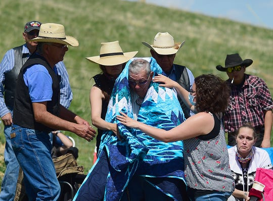 In this May 2, 2020 photo, Max Spotted Bear Sr. receives a gift blanket as friends and family gather for the funeral of his brother Bruce Spotted Bear Sr. on his ranch near Pryor, Mont. Spotted Bear and his son Bruce Spotted Bear Jr. both died of coronavirus within a few days of each other. (Larry Mayer/The Billings Gazette via AP)