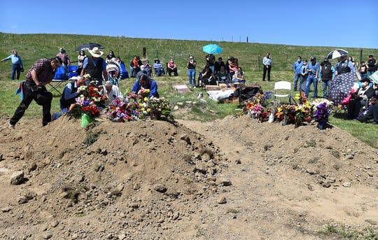 In this May 2, 2020 photo, family members pray over the graves of Bruce Spotted Bear Sr. and his son Bruce Spotted Bear Jr. on their ranch near Pryor, Mont. Spotted Bear and his son Bruce Spotted Bear Jr. both died of coronavirus within a few days of each other. (Larry Mayer/The Billings Gazette via AP)