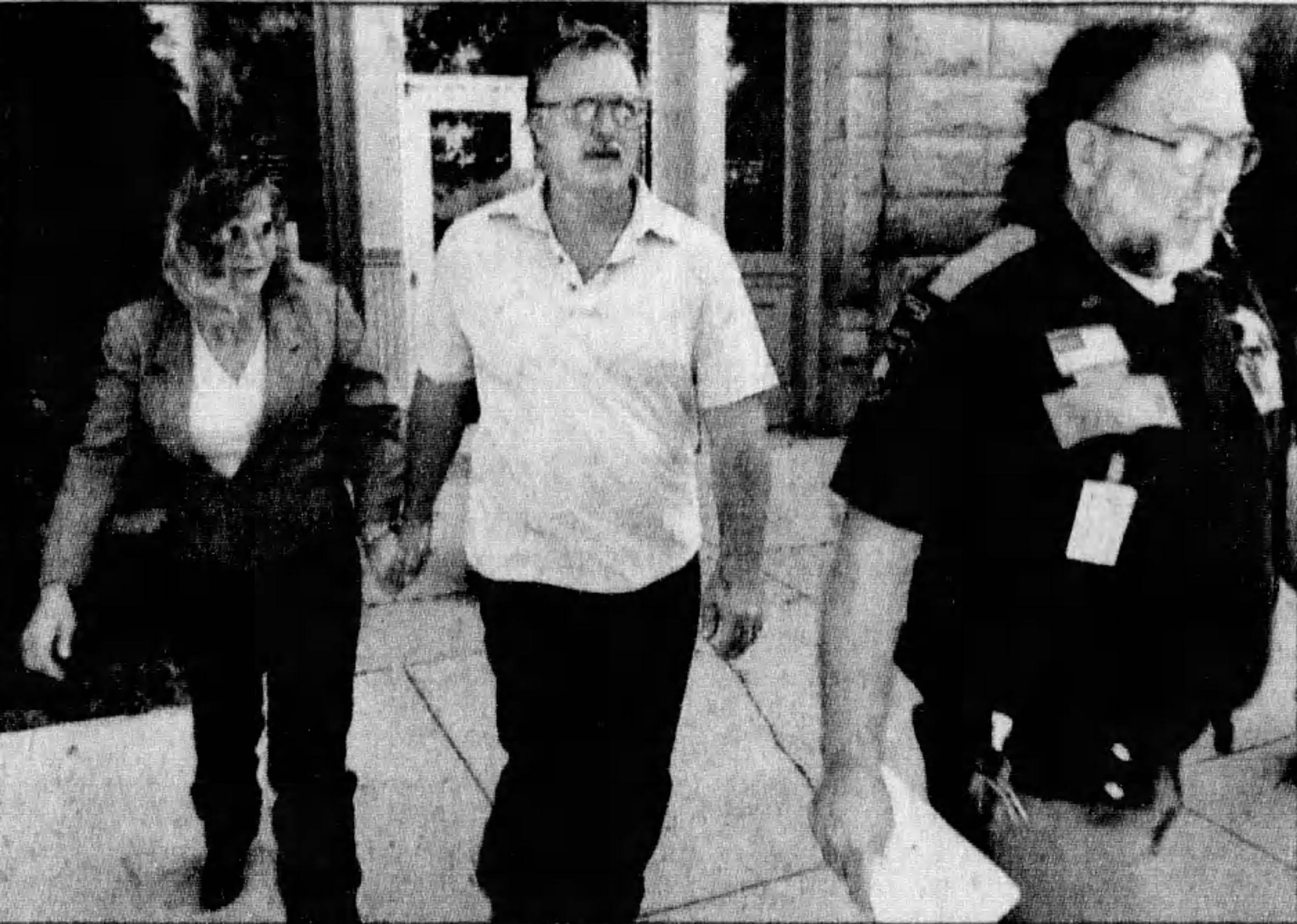 Pamela Polejewski, left and her partner Mike Hanson, center, are escorted out of court in 2005 following the seizure of more than 200 animals on their Wexford Lane property.