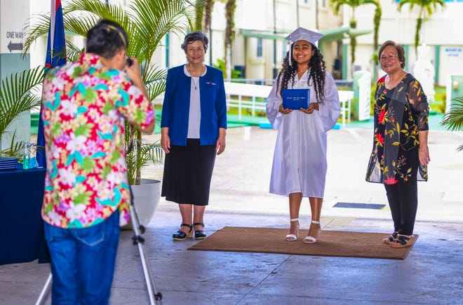 Graduating senior Hannah Therrell, center, with Sister Angela Perez, school president, left, and Principal Mary Meeks during a drive-through photo session in the Academy of Our Lady of Guam in this May 21 file photo.