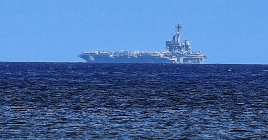 The U.S.S. Theodore Roosevelt can be seen on the horizon, from the coastline in Agat, after the vessel departed from the Naval Base Guam on Thursday, May 21, 2020. The Nimitz-class nuclear powered aircraft carrier returned to sea after pulling into port on April 27, when service members aboard  the ship were diagnosed with cases of the coronavirus.