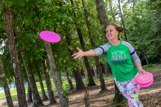 Down South Disc Golf Divas member Seprina Shepherd puts a disc into a basket during disc golf team practice at Tatum Park in Hattiesburg, Miss., Wednesday May 20, 2020.