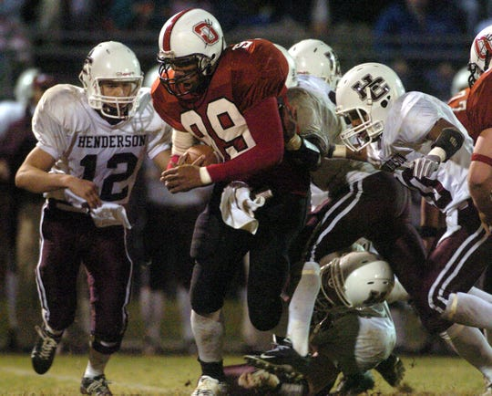 Several Henderson County players slowly bring down Owensboro quarterback Tyler Wimsatt (99) as he pushes through the line during the 2005 football game in Owensboro.
