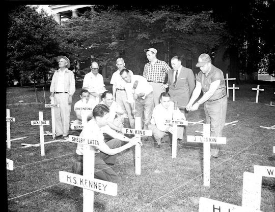 Men erecting crosses in Central Park  bearing the names of deceased Henderson County servicemen for a Memorial Day display in 1956 sponsored by American Legion Worsham Post No. 40. In 1945, the first year of the annual tradition, there were 286 crosses. By 1970 it had grown to more than 1,000. By 2004 there were nearly 3,200 crosses and in 2019 there were more than 5,300.